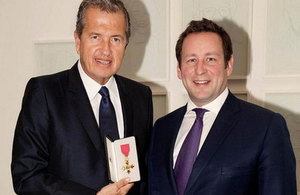 Photographer Mario Testino being presented with an honorary OBE by Culture Minister Edward Vaizey