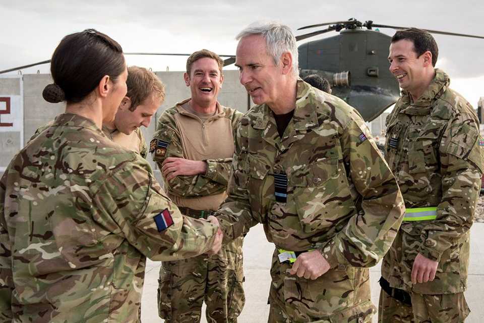 Air Chief Marshal Sir Andrew Pulford greets a soldier at Camp Bastion