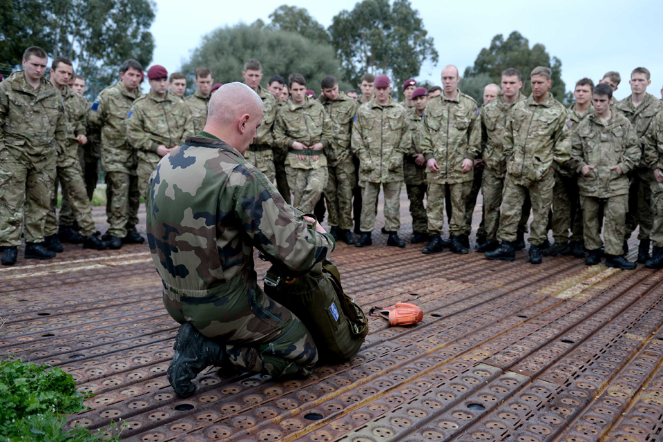 British paratroopers being instructed in how to fit a French parachute