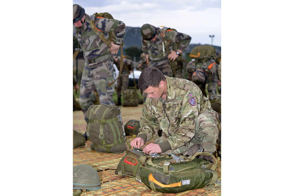Paratroopers preparing their parachutes