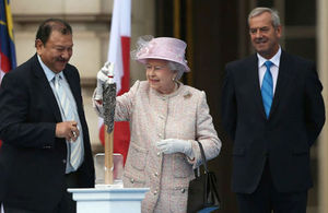 HM Queen Elizabeth II putting a message in the baton
