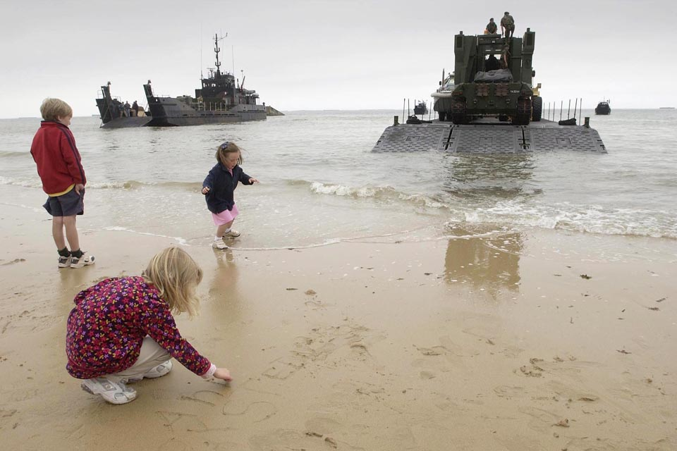 Children play on the beach at Arromanches