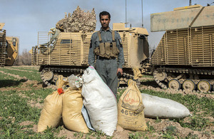 An Afghan policeman poses with bagged substances seized during the operation [Picture: Corporal Ross Fernie, Crown copyright]