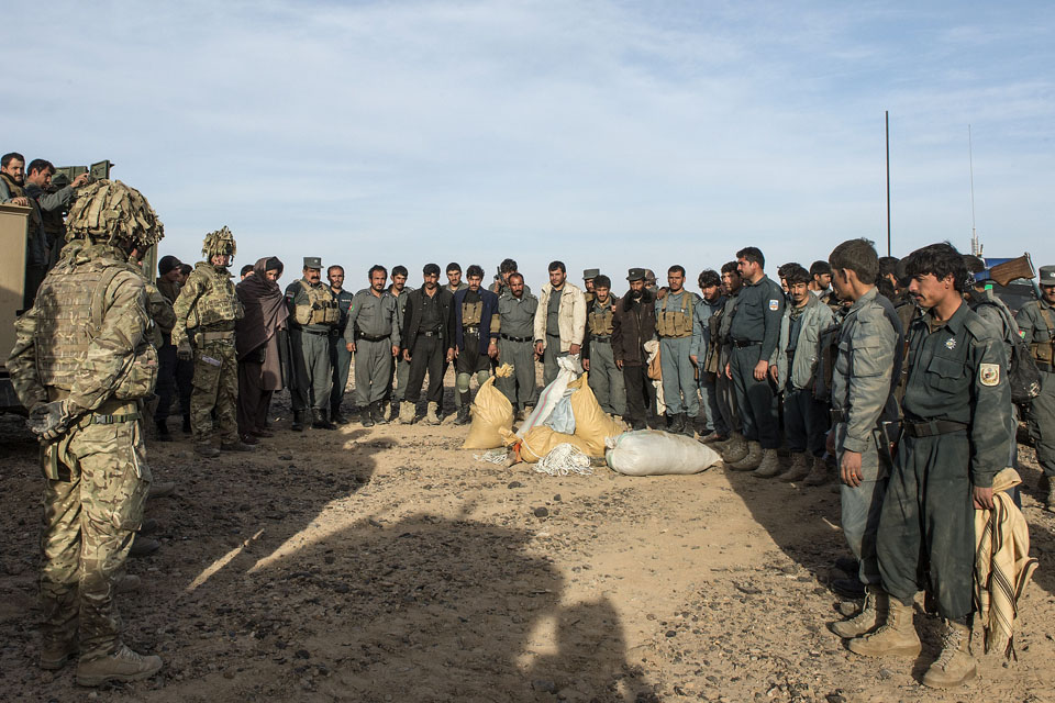 Afghan policemen and British soldiers with items seized from insurgents