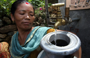 A woman collects clean water from a tap in Nepal. Picture: AusAid/Jim Holmes