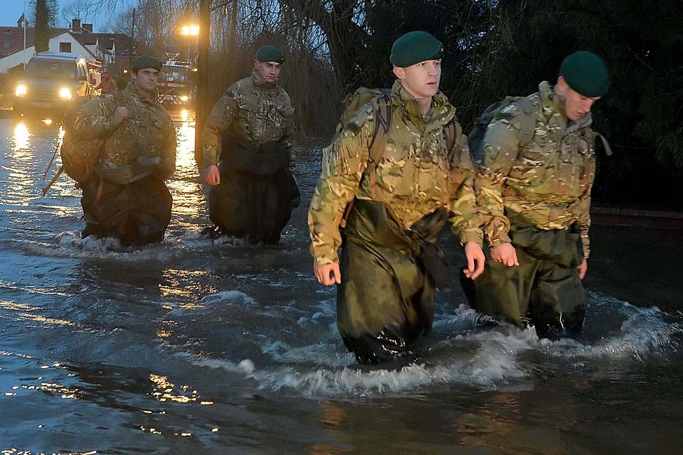 Royal Marines wade through a flooded street