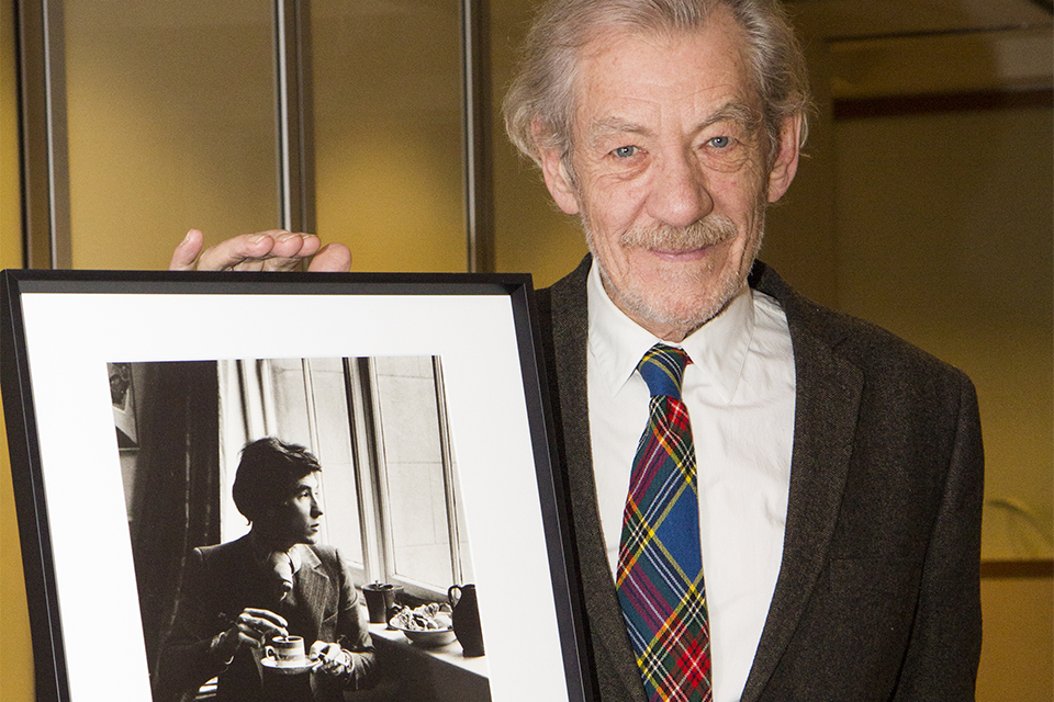 Sir Ian poses with the portrait taken by Michael Peto.