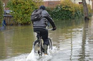 Man cycling through a flood.