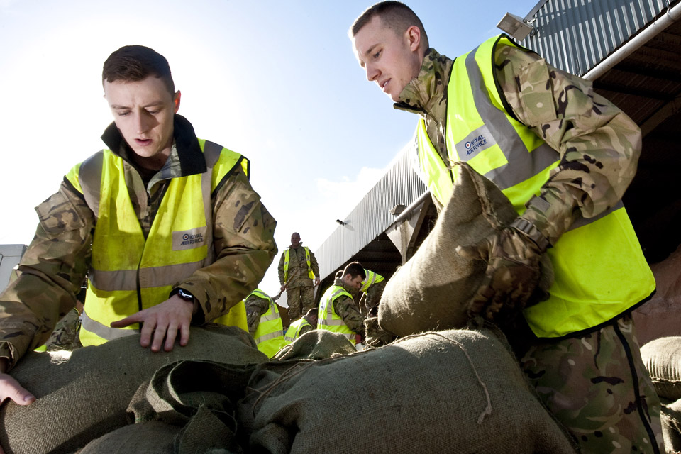 Military personnel packing sandbags