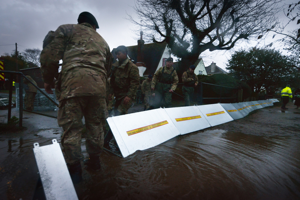 Soldiers erect flood defences alongside the River Thames