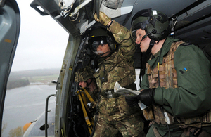 Servicemen undertaking aerial flood damage reconnaissance from an RAF Merlin helicopter [Picture: Sergeant Mitch Moore, Crown copyright]