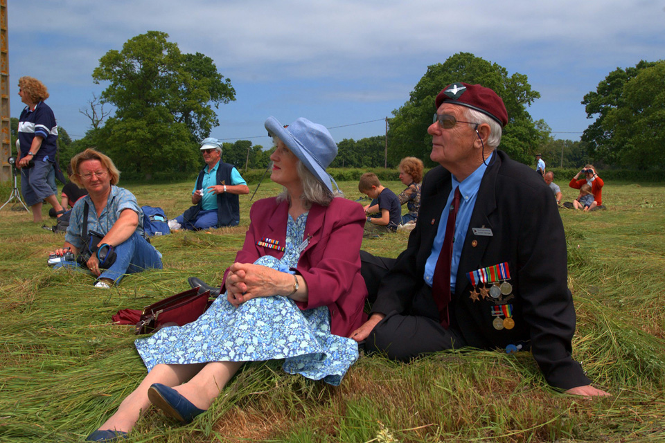 Picnicking veterans watch paratroopers jump over Normandy