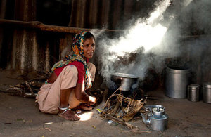 Woman cooks dinner for her family on traditional open fire in Gujarat, India.