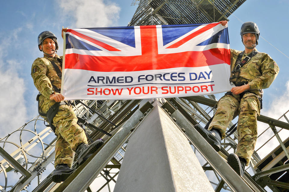 Airmen holding up the Armed Forces Day flag