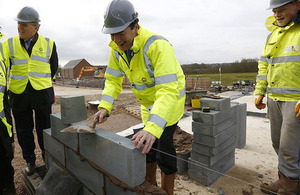 Chancellor laying a brick on a building site