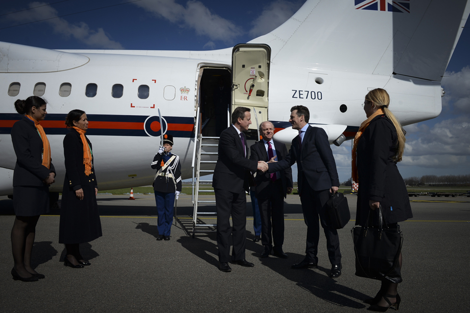 David Cameron getting off a plane and meeting officials.