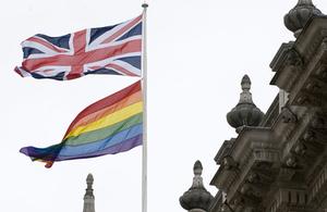 Rainbow flag and Union Jack flag on a flagpole above 70 Whitehall