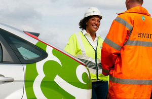 Environment Agency staff talking outside by an Environment Agency vehicle.