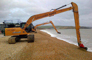 Environment Agency diggers re-profiling the beach at Preston in Devon.