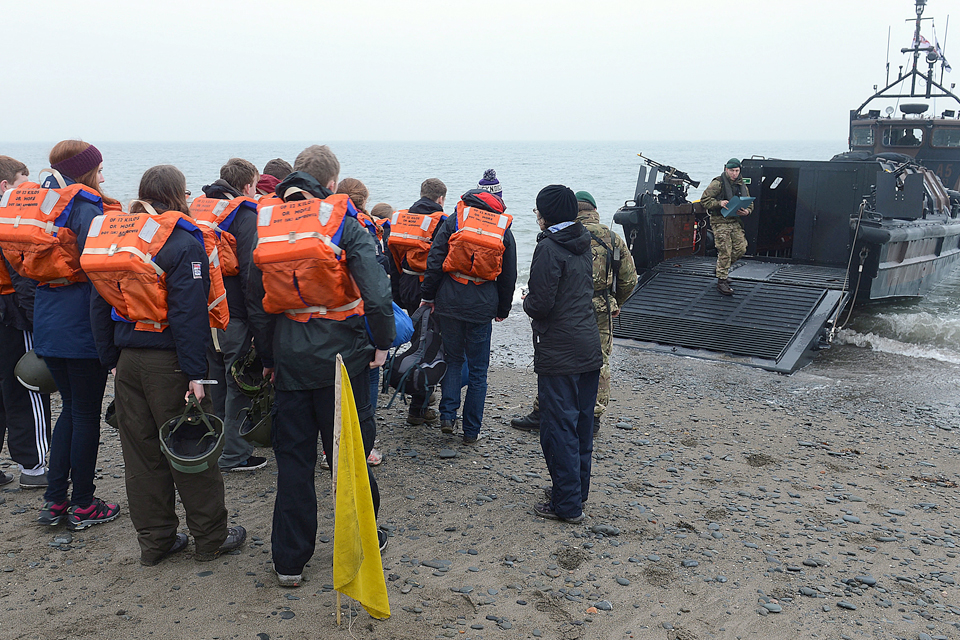 Entitled citizens are escorted onto the landing craft