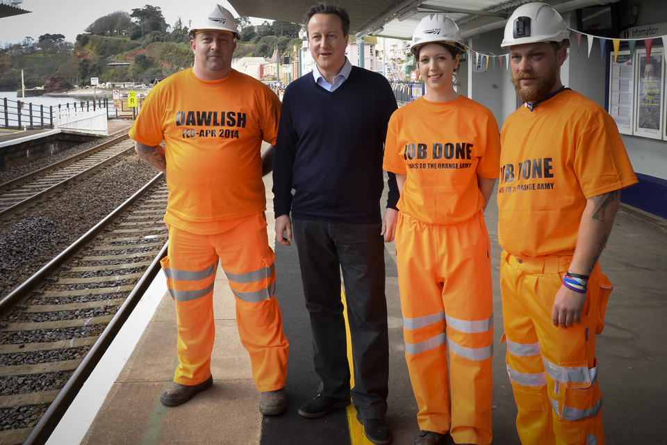 David Cameron poses with some of the 'Orange army' who helped repair the line.