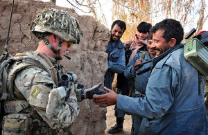 A British soldier shares a joke with members of the Afghan police during a patrol (library image) [Picture: Corporal Mike O'Neill, Crown copyright]