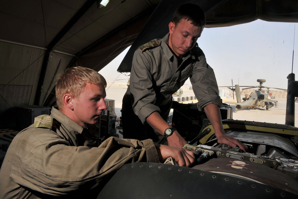Aircraft technicians service an Apache helicopter