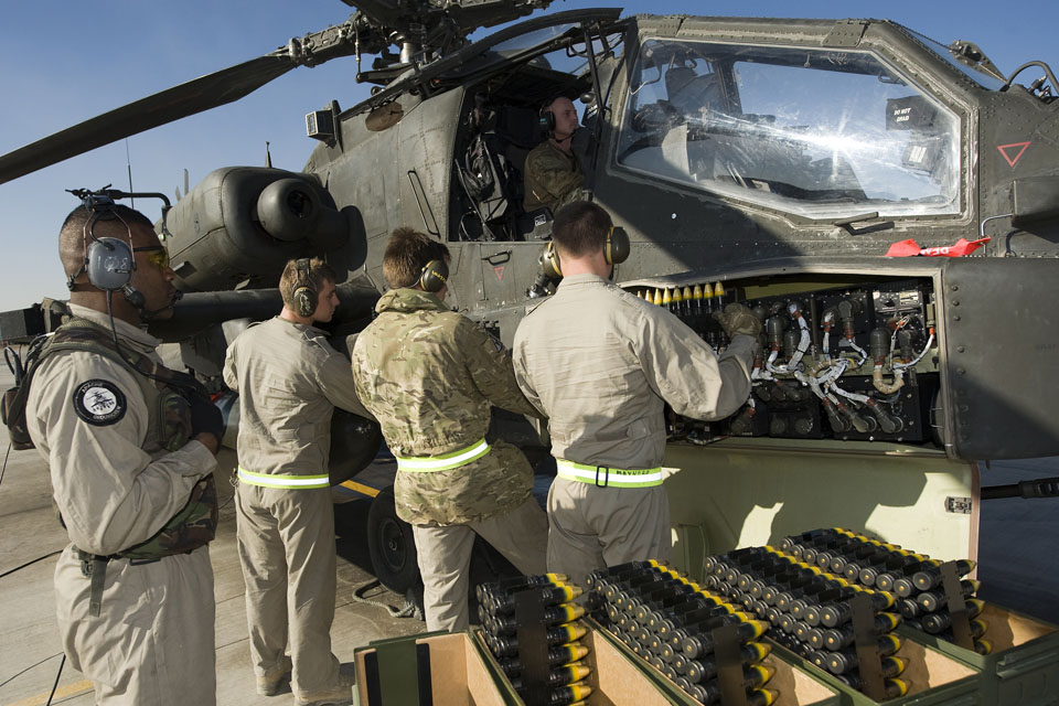 Ground crew reload ammunition onto an Apache