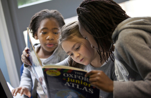 Children reading an atlas
