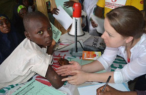 A lady examining a young african boy's arm
