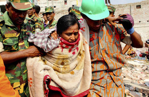 A woman is pulled from the rubble of the Rana Plaza complex in Savar by rescuers and civilian helpers.