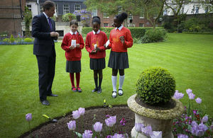 Prime minister stood in garden with flowers and school children in red uniforms