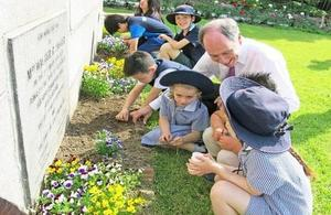 British & Korean schoolchildren plants poppies in the Residence garden