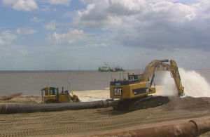 Diggers on the beach distributing sand pumped from licensed off-shore sites
