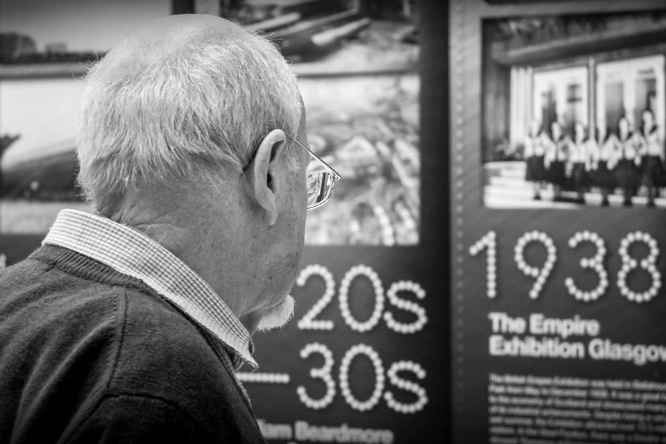 Older man looking at Glasgow art exhibition