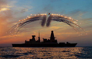 HMS Dragon's Lynx helicopter fires countermeasure flares over the ship at sunset [Picture: Leading Photographer Dave Jenkins, Crown copyright]