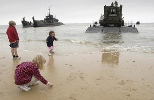 Children play on the beach at Arromanches in front of British landing craft (library image) [Picture: Giles Penfound, Crown copyright]