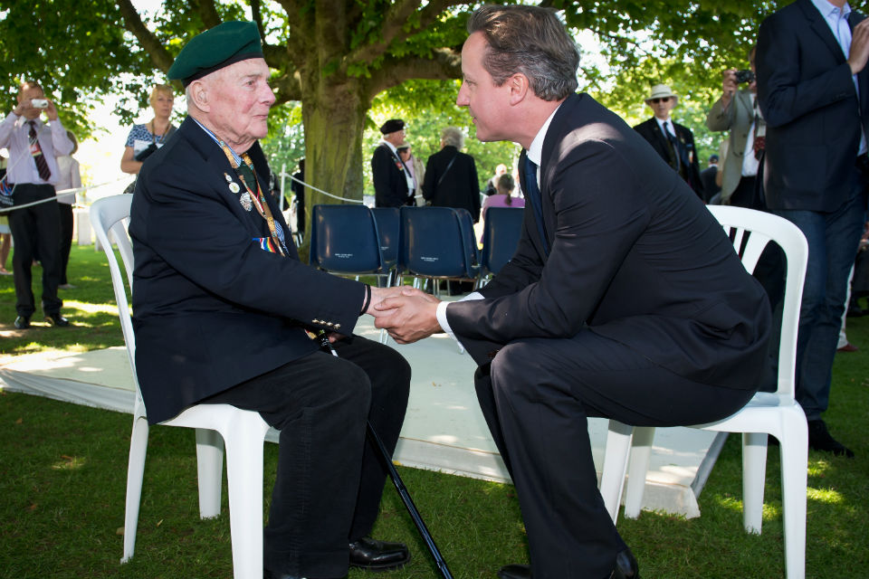 The Prime Minister with a veteran at Bayeux Cemetery.