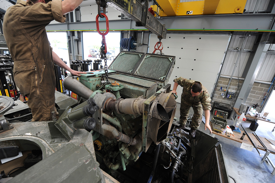 Reservist army vehicle mechanics fit an engine block