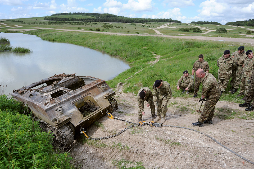 Army reservists work to extract a vehicle from a lake