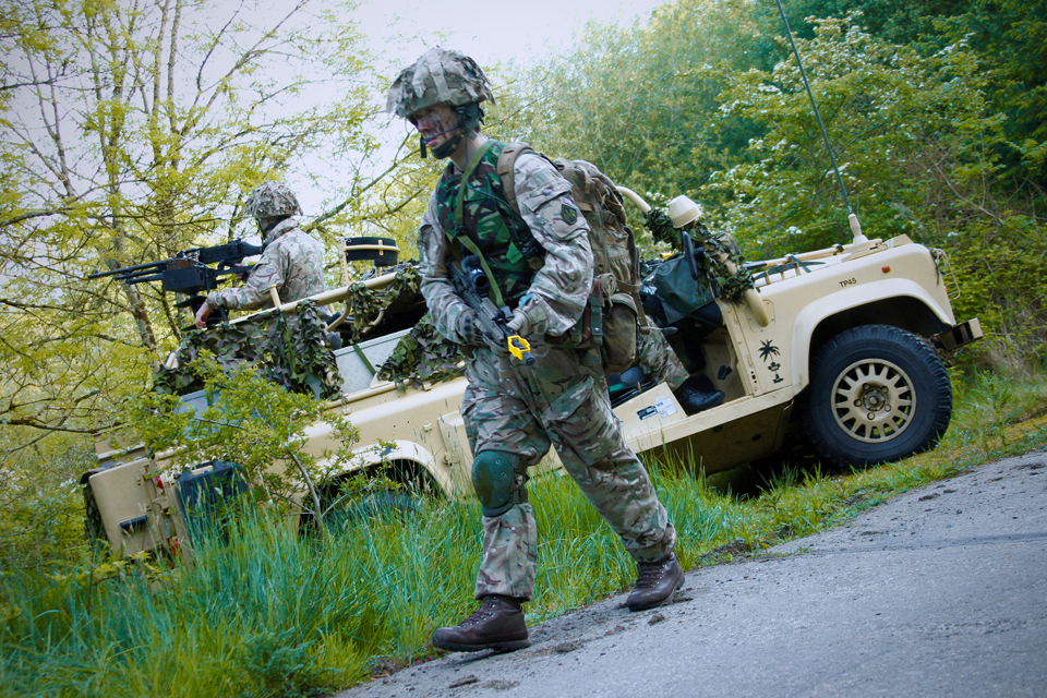 An infantry reservist patrols past a WMIK Land Rover