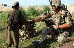 Lieutenant Tom Lucy, K Company 42 Commando Royal Marines, greets an Afghan boy whilst on patrol with his section outside of Patrol Base 5 in Helmand Province, Afhanistan