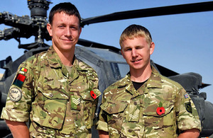 Brothers Staff Sergeant Ray Neenan and Corporal Darren Neenan in front of an Army Air Corps Apache attack helicopter at Camp Bastion in Helmand province