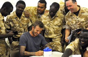 David Beckham signs autographs for soldiers from 67 Squadron, 6 Regiment Royal Logistic Corps, during his visit to Camp Bastion