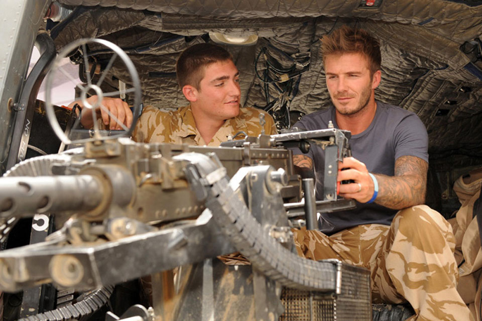 David Beckham being shown the mounted heavy machine gun on an Army Lynx helicopter
