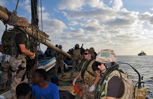 Members of a Royal Marines and Royal Navy boarding party from HMS Cornwall question suspected pirates onboard a dhow, with the Type 22 frigate visible on the horizon (stock image)