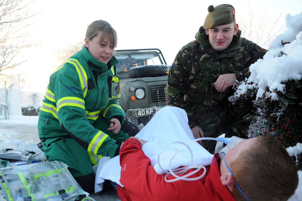 Jacqui Methven, a SORT (Special Operations Response Team) paramedic with the Scottish Ambulance Service, and territorial soldier Lance Corporal Mark McVey help a fallen casualty as local temperatures plummet to minus 14 degrees