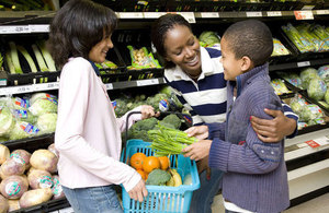 A young boy and a young girl at a supermarket with an adult woman.