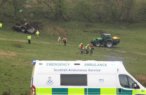The farmer who was trapped beneath his overturned tractor being stretchered to the waiting ambulance for transfer to Gannet's Sea King helicopter