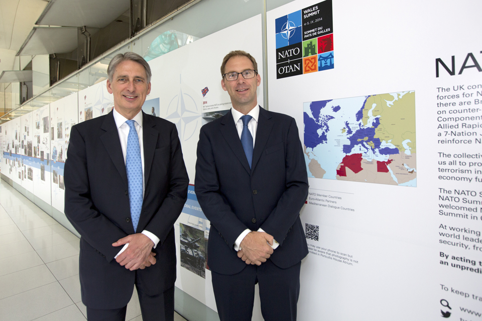 Philip Hammond (left) at the NATO 65-year timeline photographic display at Portcullis House